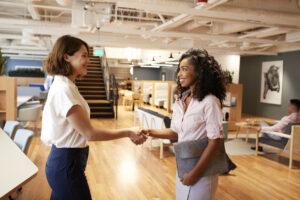 two women shaking hands in office