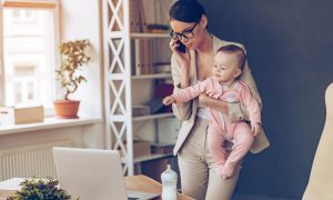 woman talking on the phone and looking at computer screen while holding a baby
