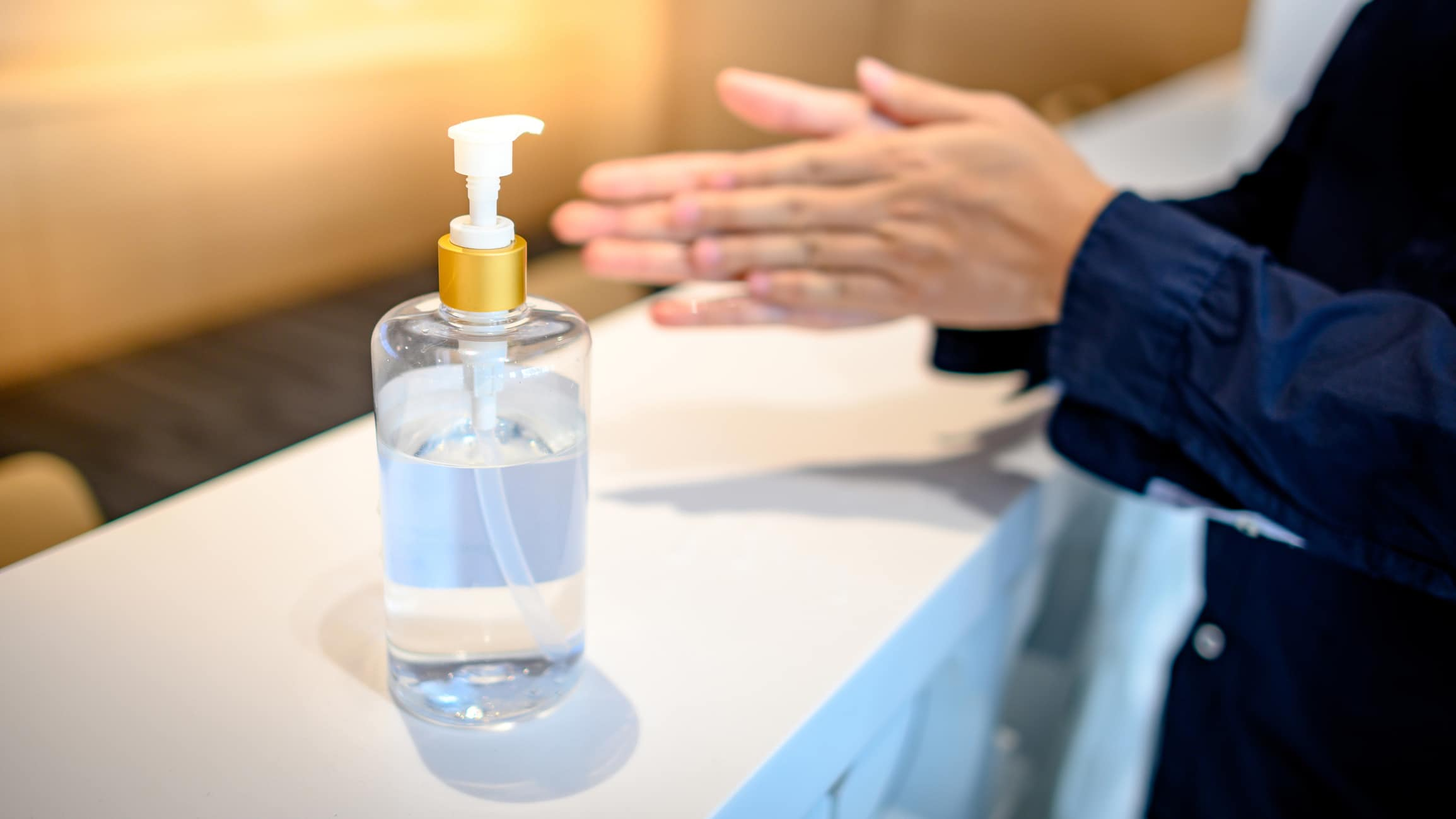 Concierge washing hands with alcohol sanitizer to prevent spreading of COVID-19