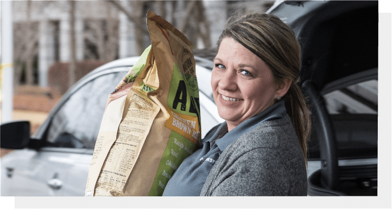 woman holding a sack of dog food