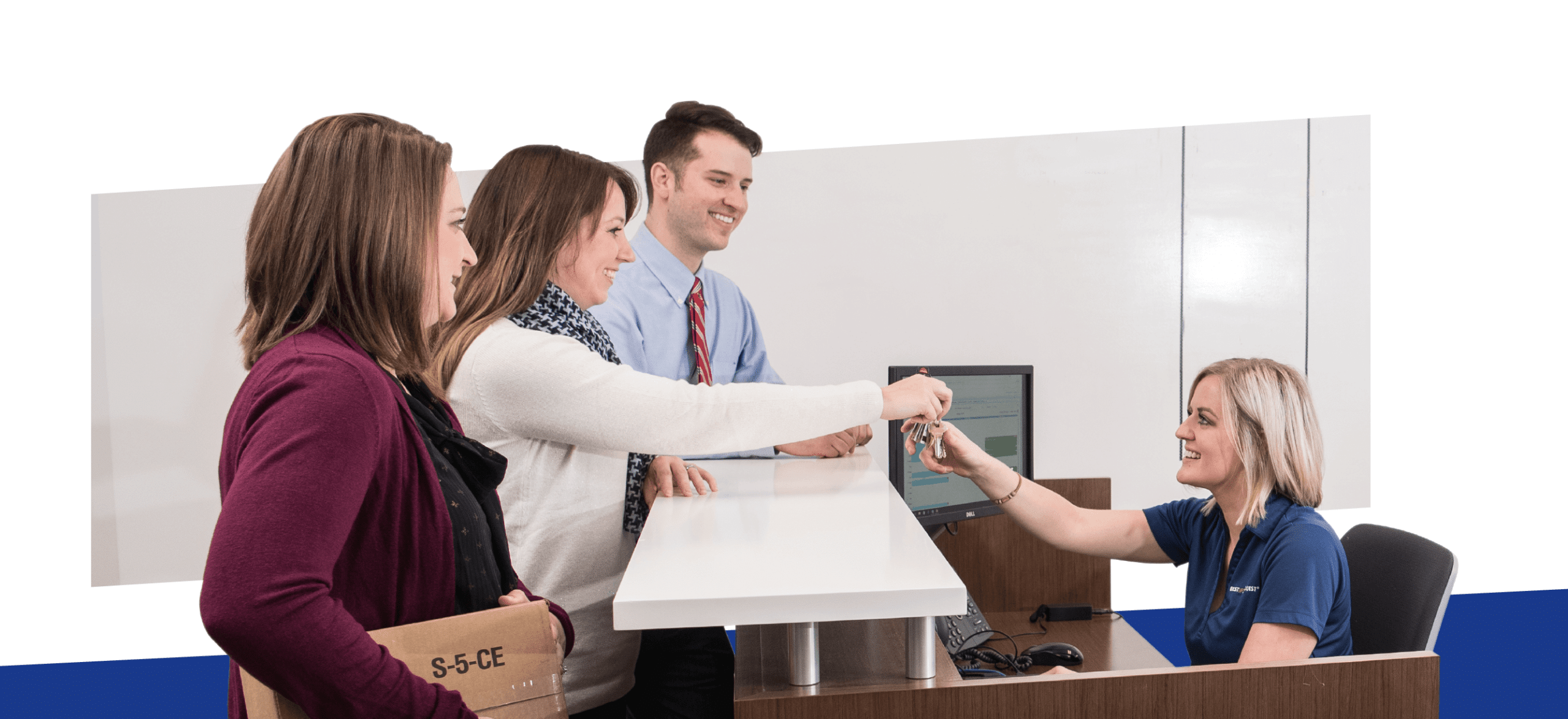 people standing around reception desk in an office