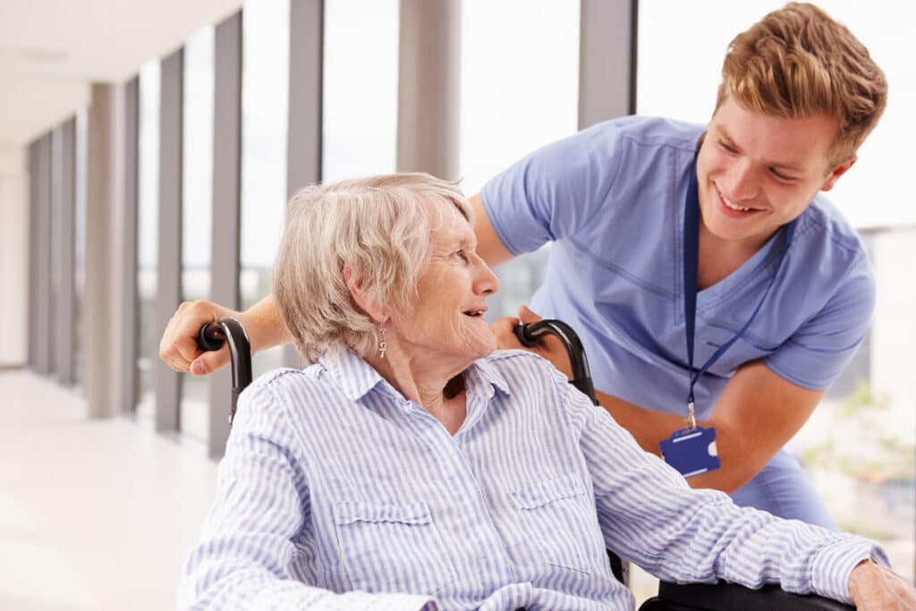 Patient Concierge Pushing Senior Patient In Wheelchair Along Corridor